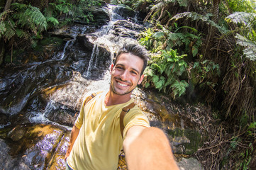 Handsome traveller taking a selfie during an excursion in a forest