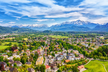 Wall Mural - Austria, Salzburg city, Europe. Spring skyline of Salzburg at the background of high mountains Alps, view from above. City scenery in green valley among trees. Harmonic existence of urban and nature.