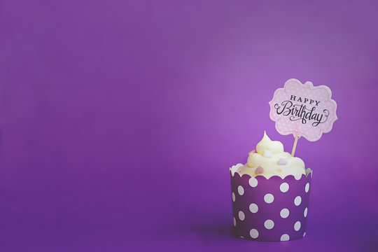 Vanilla cupcake with small decorative hearts and happy birthday sign, in violet baking paper cup, against violet background