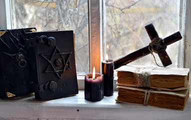 Black magic books, black candles and cross against old window. Occult, esoteric, divination and wicca concept, mystic background