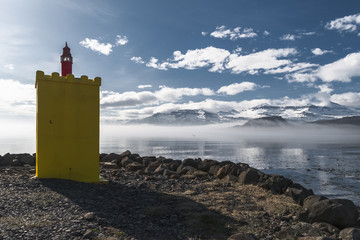 Eskifjordor Lighthouse with morning mist rising across the fjord, East Fjords, Iceland
