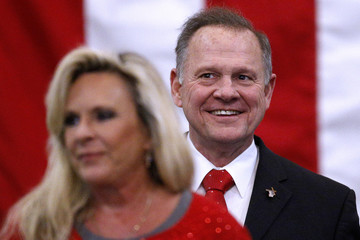 Republican candidate for U.S. Senate Judge Roy Moore smiles while his wife  Kayla delivers remarks during a campaign rally in Midland City