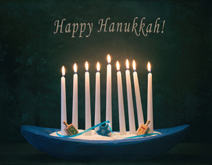 Happy Hanukkah Menorah with White Lighted Candles, Star of David Ornaments, Dreidels in dark still life with room or space for copy, text or your words. Horizontal card that is moody with cross filter
