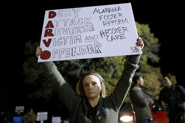 A woman holds a sign before a campaign rally for Republican candidate for U.S. Senate Judge Roy Moore in Midland City