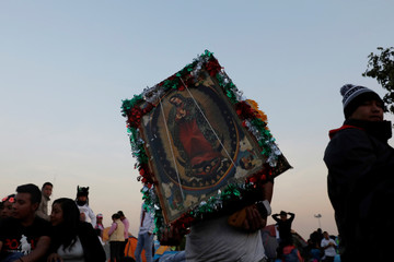 Pilgrim carries an image of the Virgin of Guadalupe during the annual pilgrimage in honor of the Virgin of Guadalupe, patron saint of Mexican Catholics, in Mexico City