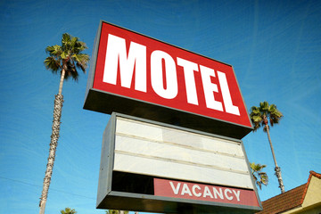 aged and worn motel sign with palm trees