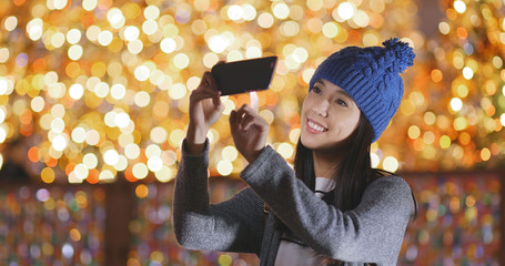 Woman taking photo on cellphone over christmas decoration background