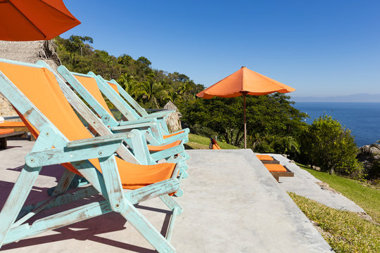 Sunbeds overlooking tropical rainforest and the bay of Puerto Vallarta, Mexico