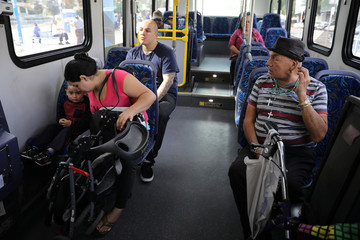 Passengers wait for an electric bus to recharge its battery in Pomona