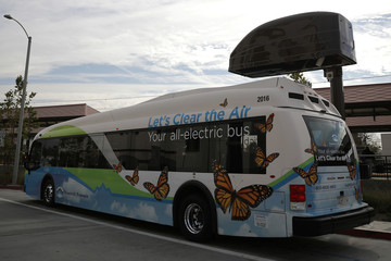 An electric bus sits under a charging station in Azusa
