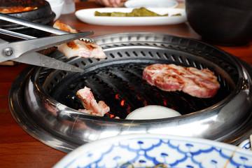 Grilling pork Korean barbecue style in restaurant