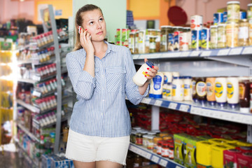 Young woman with phone choosing mayonnaise