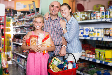 Happy family with girl standing in the supermarket