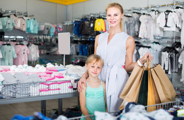 Mother with daughter holding packages with purchases in the store
