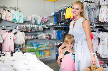 Blonde mother with daughter holding packages