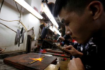 A goldsmith makes gold jewelry at a gold shop in Hanoi