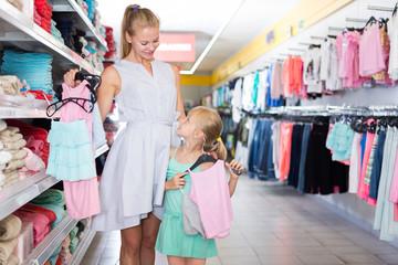 Portrait of pretty mom with girl choosing dress