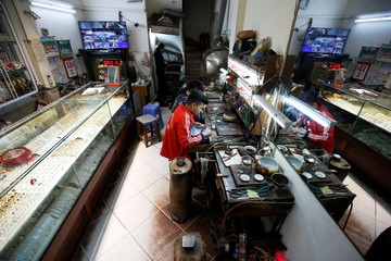 Goldsmiths make gold jewelry at a gold shop in Hanoi
