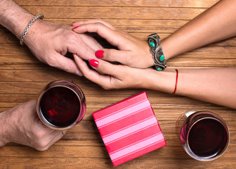 Couple celebrating a holiday. Hands with gift box and wine glasses on wooden background.