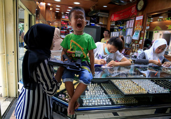 Child screams as he is accompanied by his mother buying gold ring at jewellery shop in Jakarta