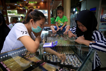Employee suggests gold ring to customer at jewellery shop in Jakarta