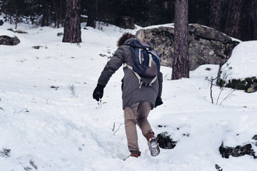 Woman walking up in the snowed mountain