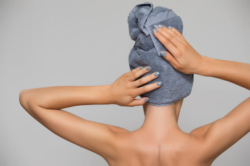 Woman with towel on head isolated on grey background. Rear view female after bath.