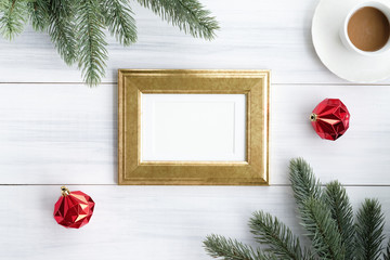 Top view of blank golden picture frame with red decoration ball, coffee , pine brance on white wood table top,Flat lay luxury holiday celebration still life,mock up for adding text,copy space