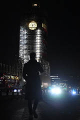 A man walks on Westminster bridge with Big Ben clock surrounded by illuminated scaffolding in the background in London