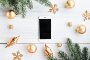 Top view of smart phone,mobile with gold decoration ball, gold ornament snowflake, pine brance on white wood table top,Flat lay  holiday celebration still life,mock up for adding text,copy space
