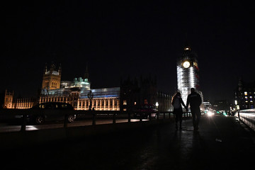 A couple hold hands crossing Westminster bridge in front of Big Ben clock which is covered in illuminated scaffolding in London
