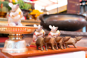 the statue of the small white and brown rat on the table in the shrine temple