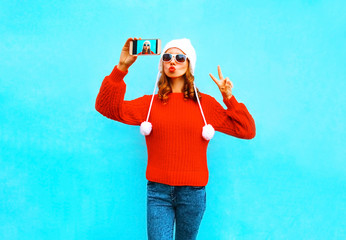 Pretty young woman takes a picture self portrait on a smartphone on blue background