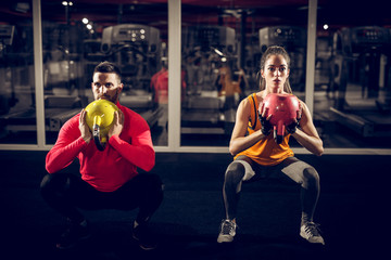 Close up front view of focused and motivated strong young fitness couple in sportswear crouching...