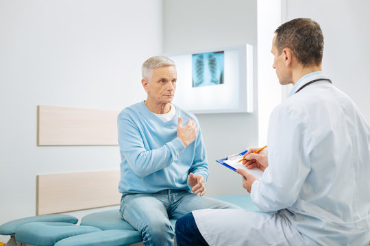 Heart problems. Nice pleasant serious man looking at his doctor and pointing at the heart while telling about his health problem