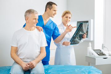 Look here. Delighted cheerful male therapist holding his patients shoulder and pointing at the X ray image while working with his colleague