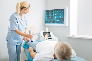 Ultrasound scanning. Nice professional pleasant doctor looking at the screen and putting a diagnosis while doing ultrasound scanning