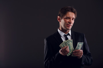 Image of man in suit counting dollars isolated on black background.