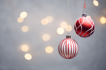 Photo of Christmas red balls on gray background with hot lights.