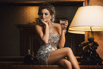 Stunning woman with a glass of cognac