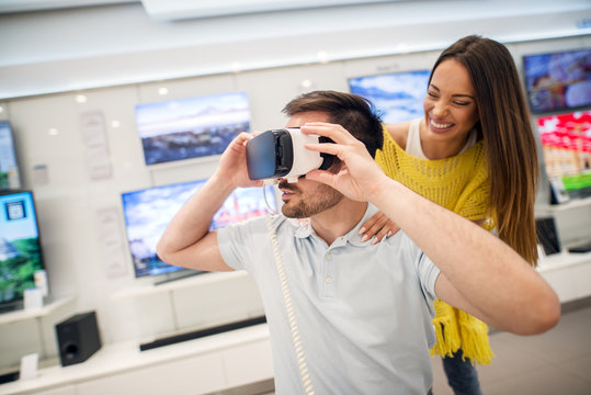 Close up view of satisfied young smiling attractive brunette girl supporting her boyfriend while testing VR goggles in a tech store.