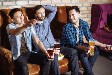 Friendship, sports and entertainment concept - happy male friends with beer watching tv at home.