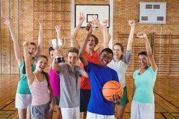 Excited high school kids holding trophy in basketball court