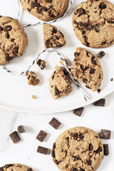 Cookies with dark chocolate chips and string on white plate.