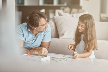 Cute positive girl drawing with her father