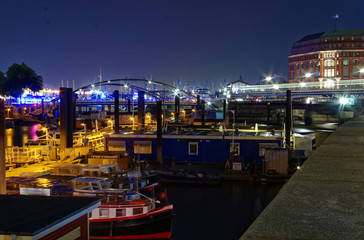 historischer Hafen in Hamburg mit Schiffen und Docks im Hintergrund und Hafenanlage bei Nacht in Deutschland Europa