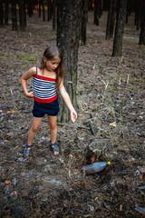 Little girl in the pine forest near the plastic bottle.