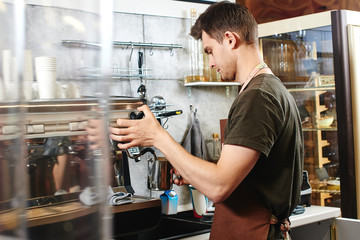 A young guy Barista works at the coffee shop.