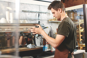 Barista at work. Guy makes coffee