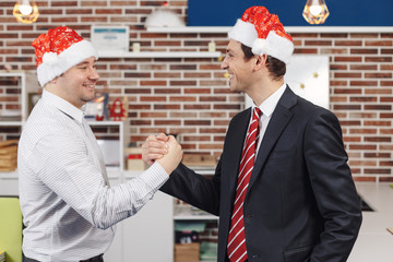 Two men shaking hands in Christmas hats